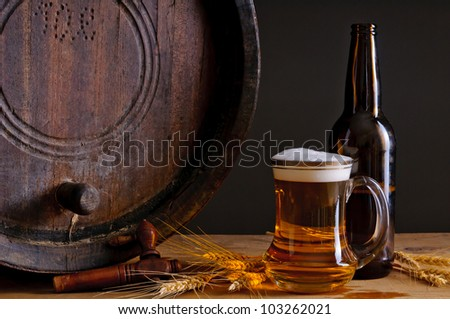 Still life composition with wooden barrel, glass and bottle of fresh beer