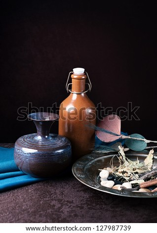 still life concept with ceramic vase and bottle with a plate made of brass on grunge background