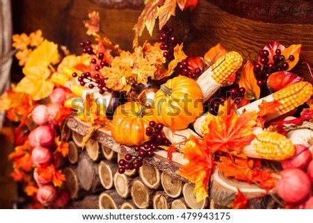 Still life consisting of orange leaves, autumn berries and vegetables: pumpkins, corns, mushrooms, peppers, garlic at the wooden background.