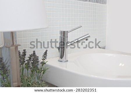 Still life detail of a bathroom sink and metallic tap against a mosaic tile wall in a white bath room at home, interior. Aspirational living bathroom washing sink in a quality luxury home, indoors. - stock photo