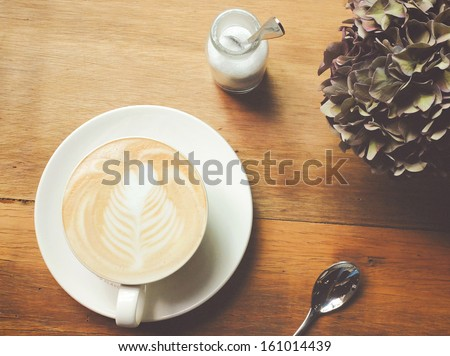 Still life details, cappuccino or latte coffee on table with retro instagram filter effect - stock photo