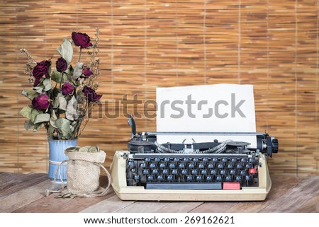 Still life Dry Rose and gold coin with typewriter on wooden - stock photo