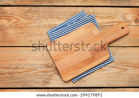 Still life, food and drink concept. Kitchen cooking utensils (cutting board, napkin) on a wooden table. Selective focus, copy space background, top view - stock photo