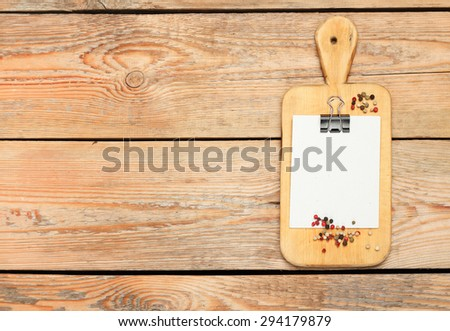 Still life, food and drink concept. Kitchen cooking utensils (cutting board with recipe) on a wooden table. Selective focus, copy space background, top view - stock photo