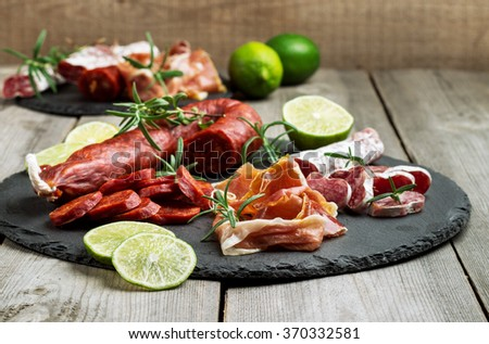 Still life, food and drink, holidays concept. Assortment of spanish tapas or italian antipasti, jamon, prosciutto, chorizo, salami on a grunge black board, rustic style. Selective focus - stock photo