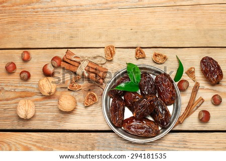 Still life, food and drink, holidays concept. Ramadan dates and spices on a wooden table. Selective focus, copy space background, top view - stock photo