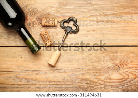 Still life, food and drink, holidays concept. Wine corks, bottle and corkscrew on a wooden table. Selective focus, copy space background, top view - stock photo