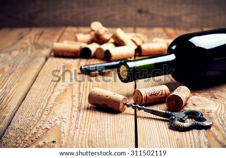 Still life, food and drink, holidays concept. Wine corks, bottle and corkscrew on a wooden table. Selective focus, copy space background - stock photo
