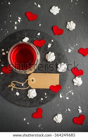 Still life, food and drink, love and holidays concept. Glass of tea, red drink and Valentine Day decoration with red hearts. Selective focus, grunge stone background, top view - stock photo