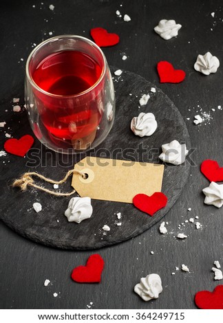 Still life, food and drink, love and holidays concept. Glass of tea, red drink and Valentine Day decoration with red hearts. Selective focus, grunge stone background - stock photo