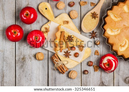 Still life, food and drink, seasonal concept. Apple pie nuts and spices (cinnamon and star anise) on a rustic wooden table. Selective focus