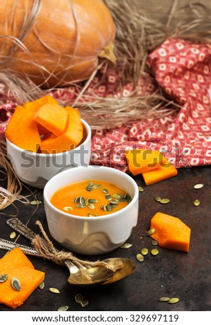 Still life, food and drink, seasonal concept. Fresh orange pumpkin soup in a bowl on a black rustic table. Selective focus - stock photo