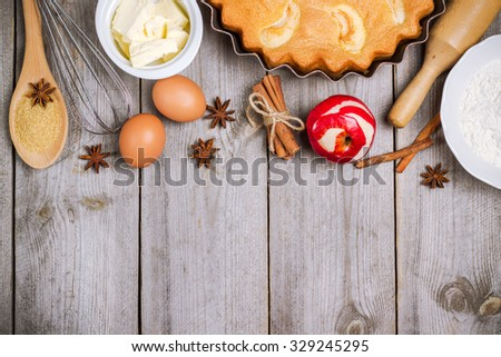 Still life, food and drink, seasonal concept. Ingredients for apple pie (red apple, flour, butter, eggs, brown cane sugar) on a rustic wooden table. Selective focus, copy space background, top view - stock photo