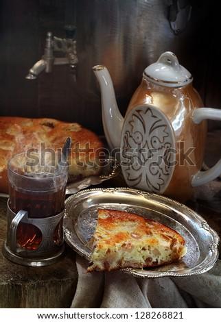 Still-life, fresh fragrant hot tea with a tasty fresh beautiful pie - stock photo