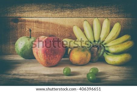 still life Fresh fruit apple grapes banana and prange with wood  - stock photo