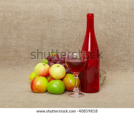 Still-life from a bottle and fruit against a canvas - stock photo