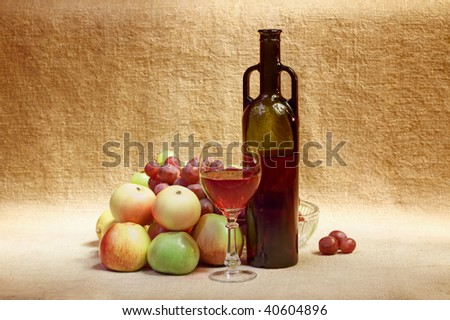 Still-life from a bottle of wine and fruit against a canvas - stock photo