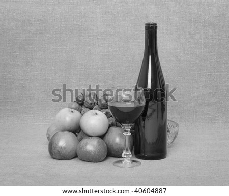 Still-life from a bottle of wine and fruit - monochrome - stock photo