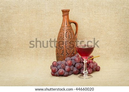 Still-life from a clay bottle, grapes and wine against a canvas - stock photo