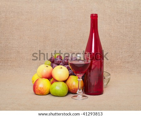 Still-life from a red bottle and fruit against a canvas - stock photo