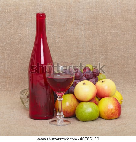 Still-life from a red bottle of wine and fruit against a canvas - stock photo