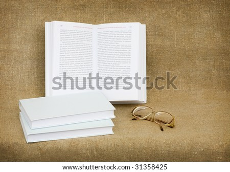 Still-life from eyeglasses and the old books - stock photo