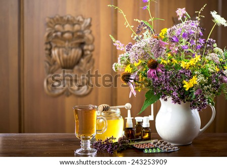 Still life from medicinal herbs, honey, herbal tea and medicines on a wooden background  - stock photo