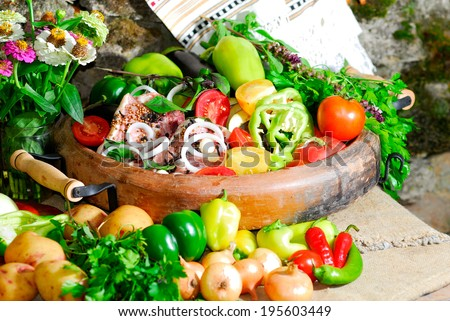 still life from vegetables and meat on the earthen dish in ethnic style - stock photo