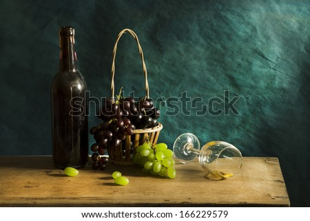 Still life fruit, Photography with Old red wine on wooden table and blue grunge background - stock photo