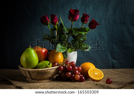 Still life fruits, fresh fruit display in wooden basket and some place on sack cloth - stock photo