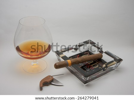 still life glass of brandy and Cuban cigars - stock photo