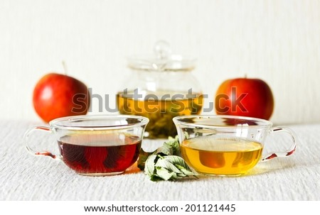 Still life: green tea in glass teapot, green and strong black tea in glass cups, mint leaves, fruits: apples