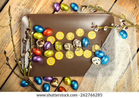Still life, holidays, food and drink concept. Easter decoration with quail and chocolate eggs and willow branch. Top view, selective focus - stock photo