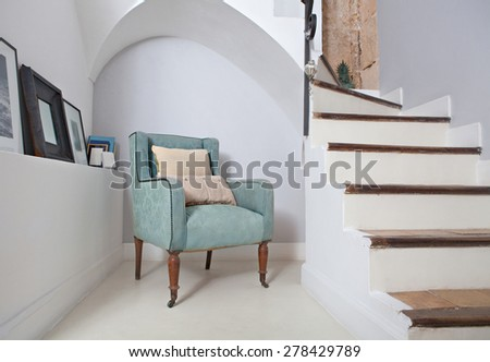 Still life home interior of an elegant armchair in a stylish home with cushions under an arch and next to stone walls and stairs, indoors. Reading room with picture frames, aspirational lifestyle. - stock photo