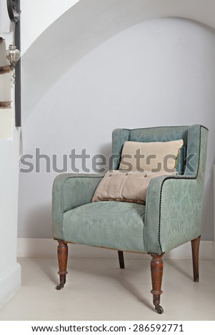 Still life home interior view of a traditional quality and luxurious wooden armchair with cushions in a stylish home living room, indoors. Elegant reading room with upholstery chair, empty space. - stock photo
