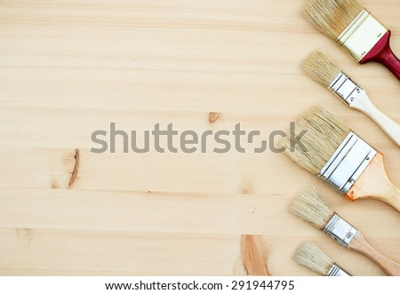 Still life, house and garden concept. Paint brushes on a wooden background. Selective focus, copy space background, top view - stock photo