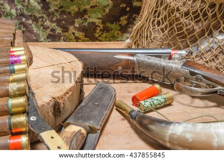 Still life. Hunting gun, bag, bandoleer, cartridges, hunting horn, knife, feathers on a wooden background - stock photo