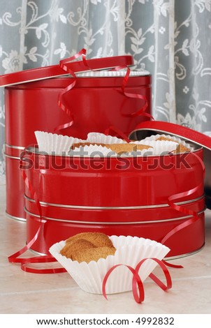 Still-life image of red gift tins filled with baked cookies.  Old-fashioned lace background and curls of red ribbon added for accents. - stock photo