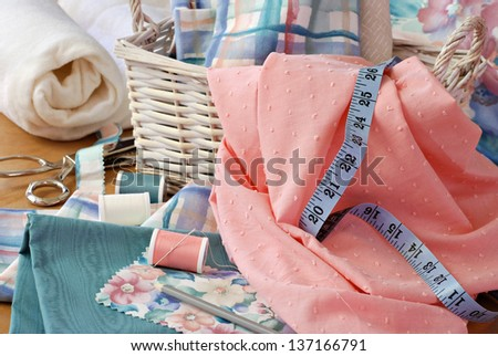 Still life image of sewing basket with pretty pastel fabrics and supplies for home decor or quilting project.  Roll of cotton batting and pinking shears in background.  Closeup with shallow dof. - stock photo