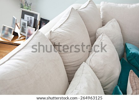 Still life interior design home living room with comfortable white sofa with cushions, and family picture frames in a home interior, close up detail. Aspirational home family room, indoors lifestyle. - stock photo