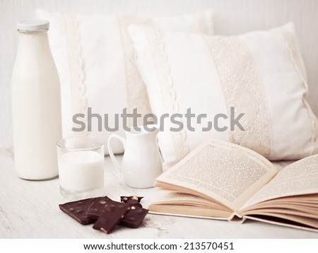 Still life interior details, glass of milk, chocolate and a book near white cozy pillow - stock photo