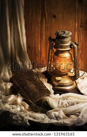 Still life. Lantern, old book and rose. - stock photo