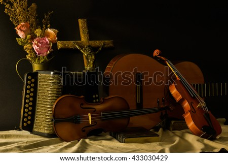 still life ,light and painting ,jesus cross violin guitar accordion on black background - stock photo