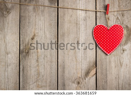 Still life, love and holidays concept. Red heart hanging on the clothesline for Valentines Day. Selective focus, copy space rustic wooden background - stock photo