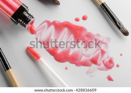 Still life made of beauty products and tools for putting on the make-up. Poured out from its tube pastel pink lipstick in stains and drops on the white table. - stock photo
