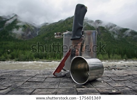 still life metal flask, mug and a knife on the background of the river and the mountains in the clouds - stock photo
