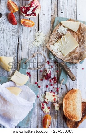 Still life of a antipasto of toast with cheese, clementine, pomegranate, pear  on a rustic table with whole grain bread. Meal is served on a table with boiled eggs. Authentic natural food. - stock photo