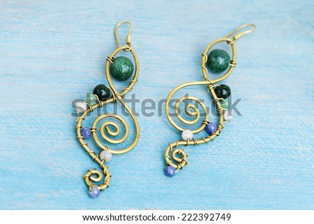 Still life of a hand made tribal ethnic earings resting on light blue painted wood. - stock photo