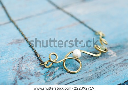 Still life of a hand made tribal ethnic necklace against light blue painted wood. - stock photo