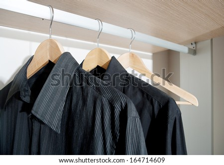 Still life of a professional hotel room wardrobe with a business man tidy black shirts hanging from wooden hangers. Home interior detail with no people.